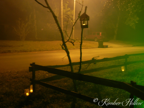 Children, adults, and ghosts follow the path marked by candle lanterns.