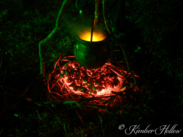 A golden potion simmering over hot, glowing coals.